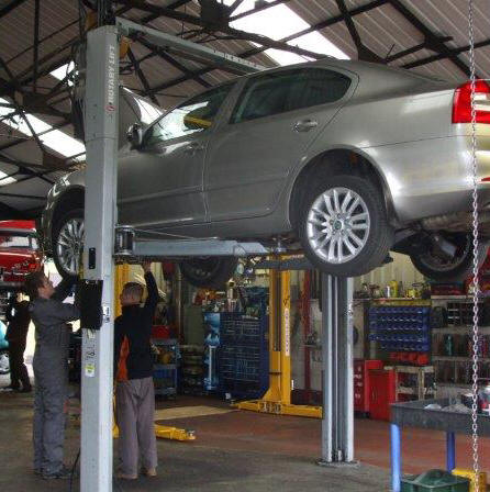 Mechanics working underneath Skoda Octavia